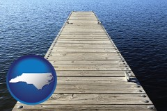 north-carolina map icon and a boat dock on a blue water lake
