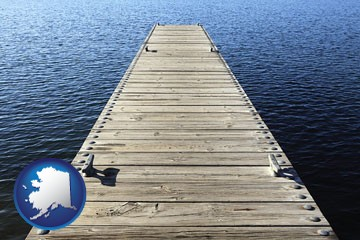 a boat dock on a blue water lake - with Alaska icon