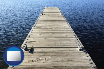 a boat dock on a blue water lake - with Colorado icon