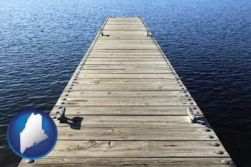 a boat dock on a blue water lake - with Maine icon