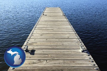 a boat dock on a blue water lake - with Michigan icon