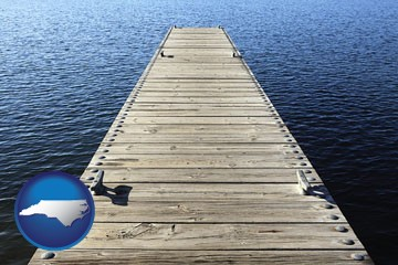 a boat dock on a blue water lake - with North Carolina icon