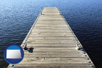 a boat dock on a blue water lake - with North Dakota icon