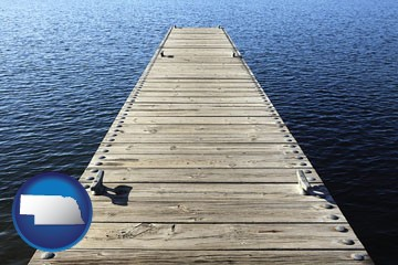 a boat dock on a blue water lake - with Nebraska icon