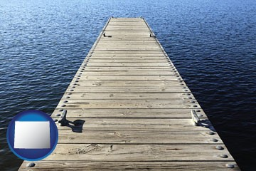 a boat dock on a blue water lake - with Wyoming icon